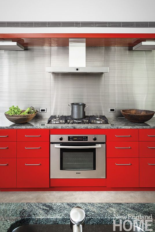 Red, metal cabinetry stands in contrast to the many shades of gray ...