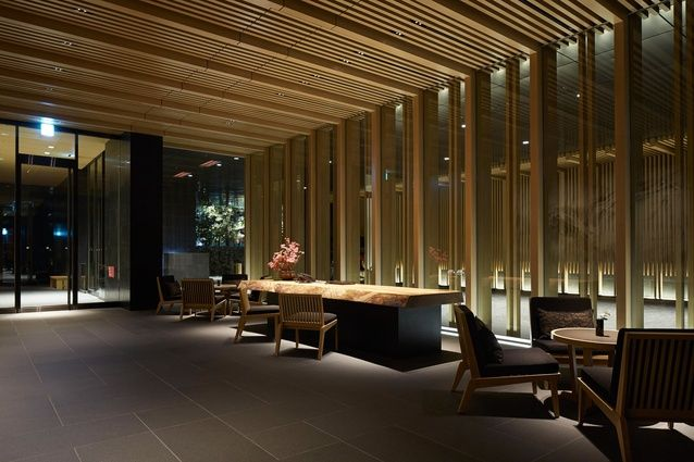 Guests enter the hotel via a dimly lit lobby off the ground-level porte-cochere.