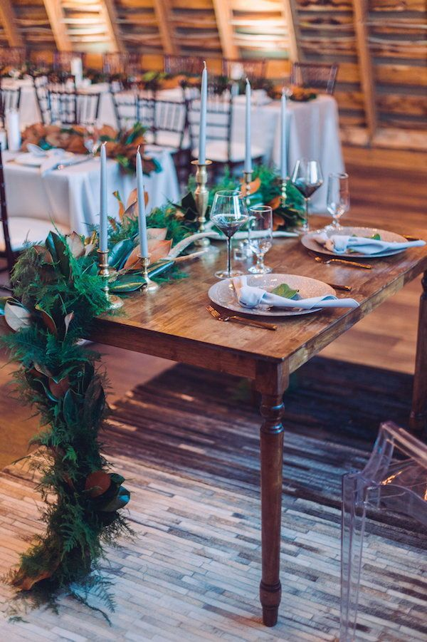 A vintage wood table with turned legs decorated with evergreen garland with magnolia leaves and taper candles in gold candle holders served as the sweetheart table at this Northern Virginia winter wedding.  #sweethearttable #weddingtable #tablescape #winterwedding #tabledecor #vintagewedding #barnwedding #virginiawedding
