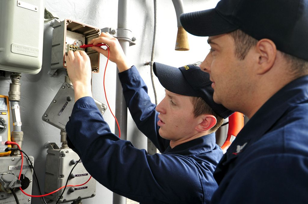 Sailors check for voltage on an aircraft carrier elevator bell - contractor job description