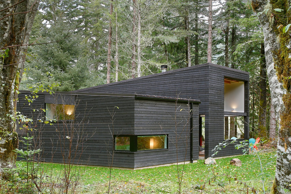 Photo of Blackened wood house by Robert Hutchison provides retreat in Seat