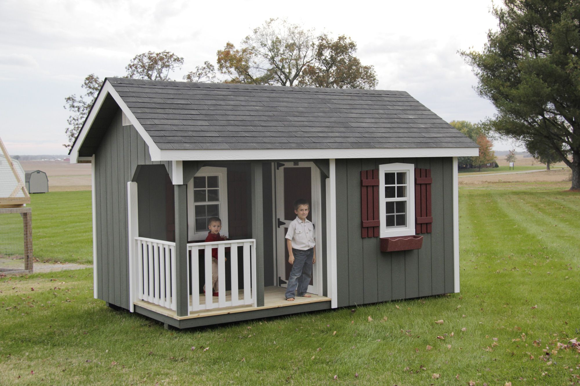 an a roof style outdoor kids playhouse with green wooden siding