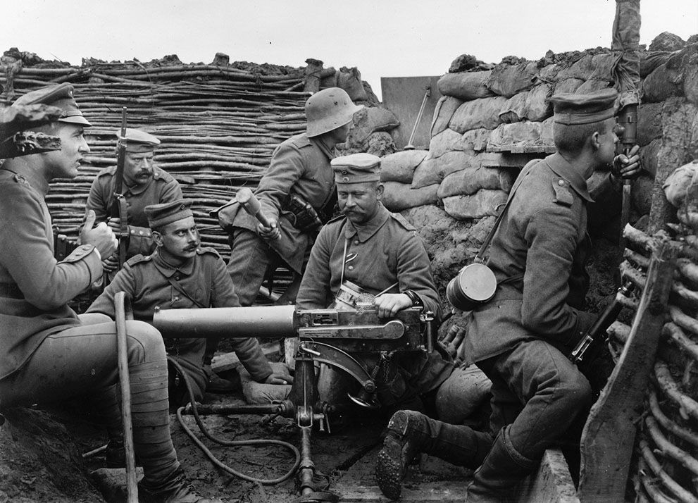"""Six German soldiers pose with machine gun, a mere 40 meters from the British line. The machine gun appears to be a Maschinengewehr 08, capable of firing 450-500 rounds a minute. The large cylinder is a jacket around the barrel, filled with water to cool the metal during rapid fire. The soldier at right, with gas mask canister slung over his shoulder, is peering into a periscope to get a view of enemy activity. The soldier at rear, with steel helmet, holds a """"potato masher"""" model 24 grenade."""
