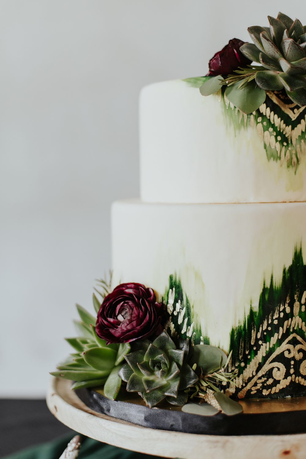 Southwestern and bohemian wedding cake with black, gold and green ...