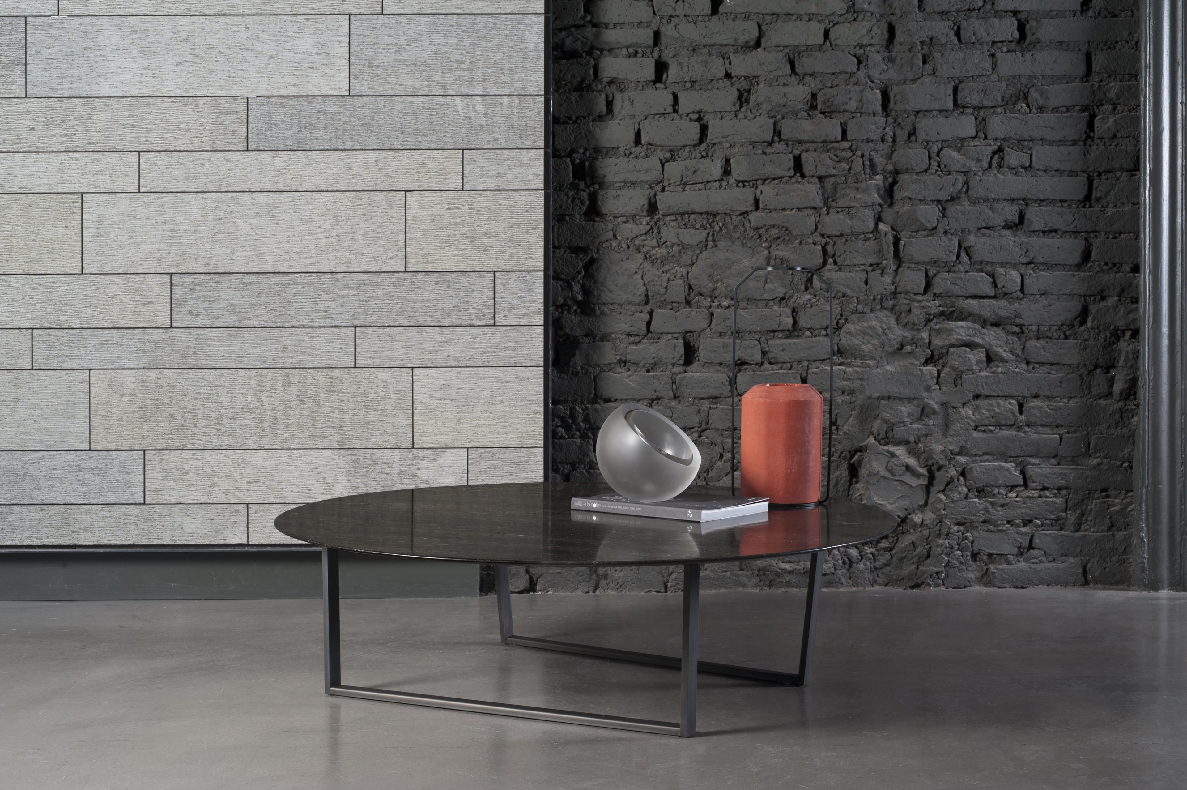 Designed by Piero Lissoni exclusively for Salvatori, Dritto combines elegant lines of classic natural stone with a bold geometric frame crafted from iron. Its defining characteristic is the curved underside of the top, and  its uber-fine edges of a mere 5 mm which give the impression of a lightness and delicacy rarely associated with stone.  Prices are indicative only as they depend on the size of the table.