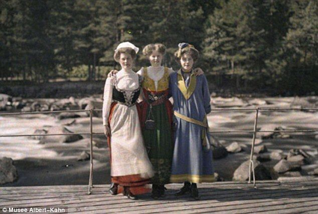 Bygone time: Three colourfully-dressed women stand next to a rocky beach in Sweden