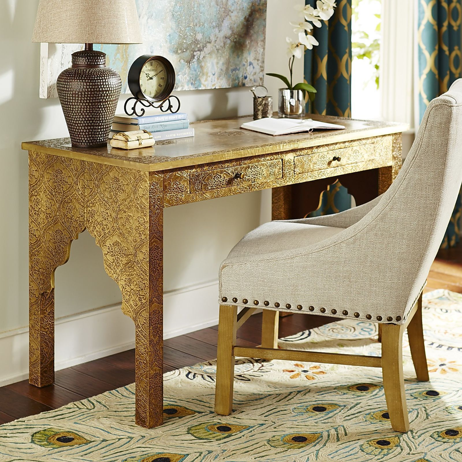 Our Moroccan-inspired, hand-embossed, two-drawer desk is hand-painted in the golden tones and patterns of an exotic Arabian tapestry. Cutouts of traditional Middle Eastern arches speak directly to the table's cultural origins. Quite the conversation piece, this one.