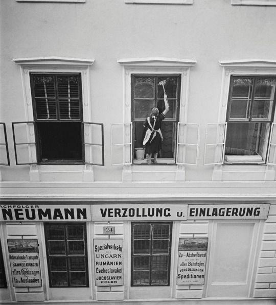 Roman Vishniac. Woman washing windows above Mandtler & Neumann Speditionen (Mandtler & Neumann Forwarding Agents), Vienna, 1930s.
