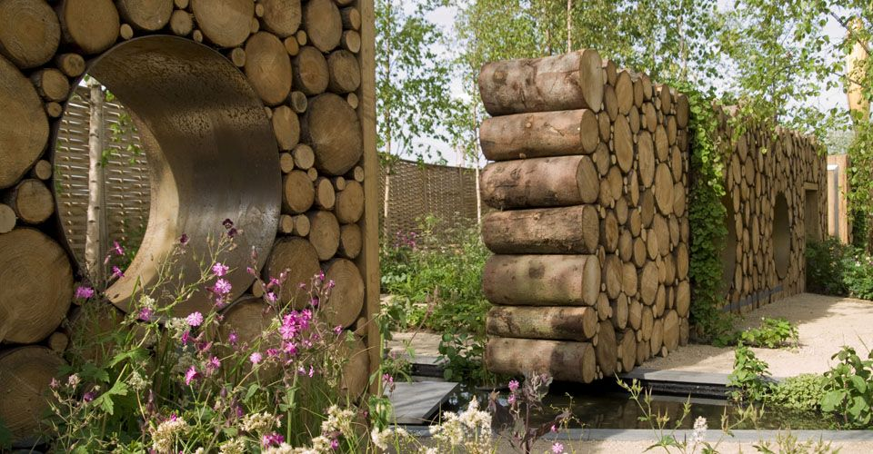 Wood log wall in garden with eyelets.  Hugo Bugg landscape design
