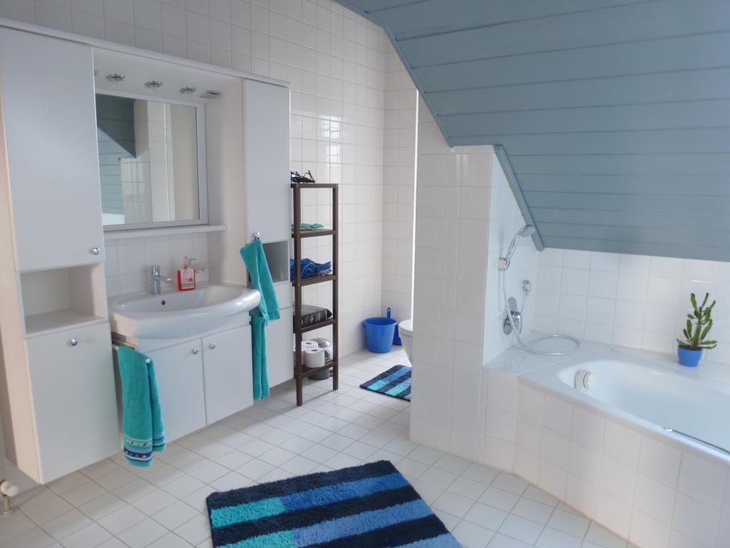 Großes Badezimmer mit weißen Fliesen, blaugrauer Dachschräge sowie ...