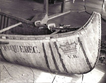 Bow view of  25' fur-trade type birch bark canoe , ''THE QUEBEC'', under repair by Henri Vaillancourt and Rick Nash in 1972. It features the royal crown painted on both ends with the initials V.R. [ Victoria Regina ] underneath.