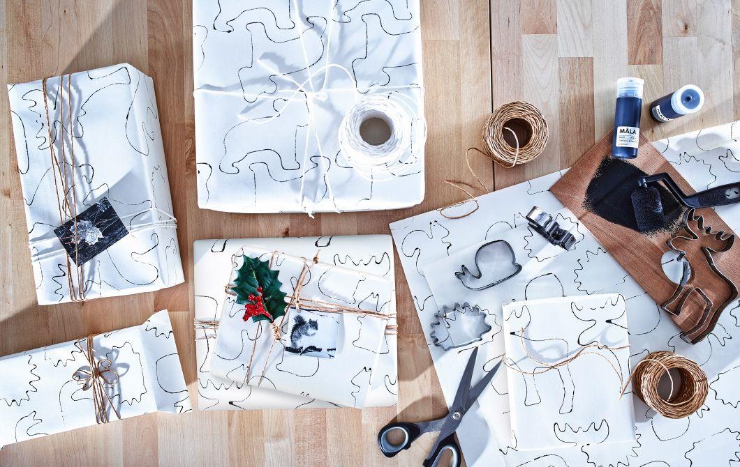 Visão panorâmica de caixas embrulhadas sobre uma mesa de madeira. Também surgem todos os elementos utilizados para se fazer papel de embrulho, incluindo tinta, cordão, tesoura e formas corta-massa, junto das caixas.