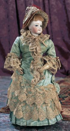 """Theriault's Antique Doll Auctions - Rare French Bisque Poupee with Deposed Molded Leather Body by Clement - 14"""" Bisque swivel head on kid-edged bisque shoulder plate. Grey glass enamel inset eyes. Hollow molded leather body with dowel jointing - circa 1870 - Very rare deposed model doll is well preserved,and wears a beautiful antique aqua silk gown,undergarments,bonnet,shoes."""