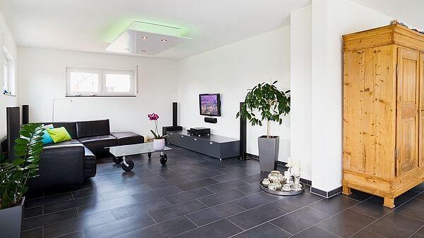 Wohnzimmer dunkle Bodenfliesen weiße Wände schwarze Ledercouch