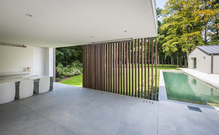 Slim vertical screen modern poolhouse crépi met hout bogarden