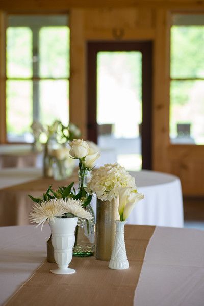 Simple wedding centerpiece idea - burlap runner with white flowers in assorted vases {Thirteenth Moon Photography LLC}