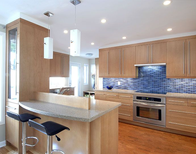 Open Concept Kitchen With Eat In. The Contrast Of The Blue Glass Backsplash  Brightens