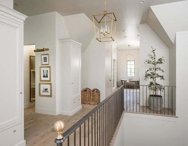 A Darlana Medium Lantern Hangs From A Shiplap Ceiling Over A Second Floor Landing Clad In Pine Wood Floors Lined Iron Staircase Railing Home Wood Floor Design