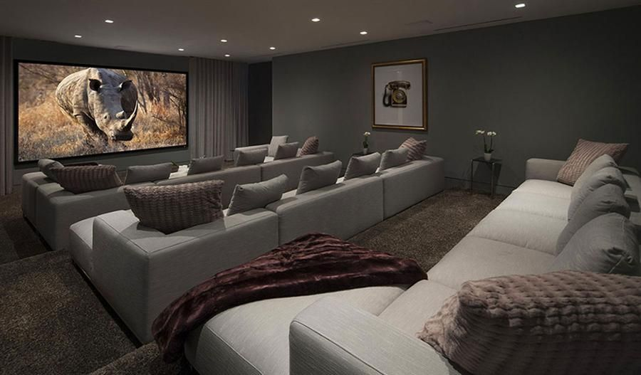 Spacious Home Cinema With Comfy Couches In Soft Gray And Large Screen Of Tv Home Cinema Room Home Theater Rooms Home Theater Seating