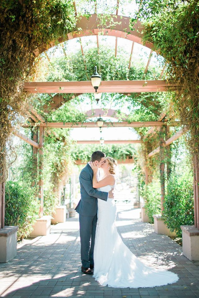 The bride and groom kiss under our vine covered archway