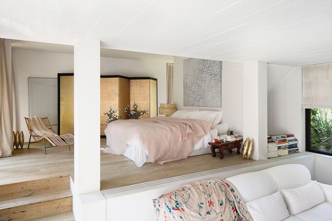 A White Walled Bedroom With A White Bed And A Rose Colored Throw
