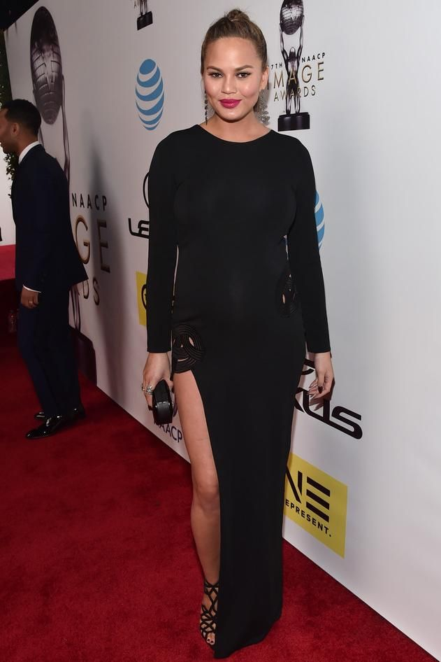 Chrissy Teigen wearing Giuseppe Zanotti Raquel Cutout Suede Sandals and Haney Gia Gown
