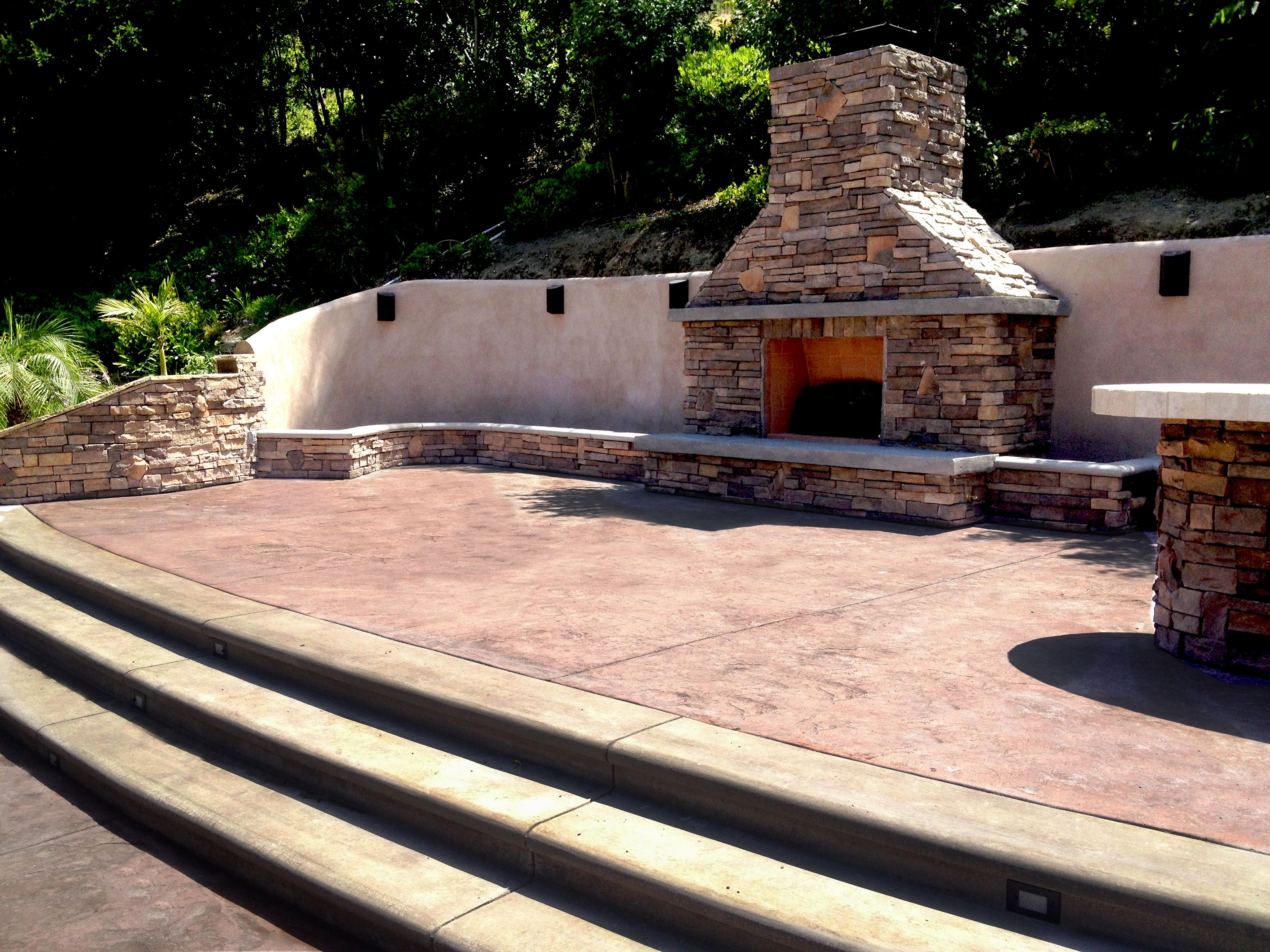 Outdoor fireplace retaining wall stamped concrete