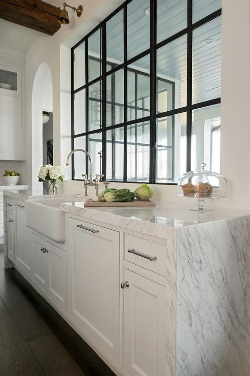 Beautiful transitional kitchen features a white and gray marble waterfall countertop on white shaker cabinets finished with chrome hardware. #waterfallcountertop
