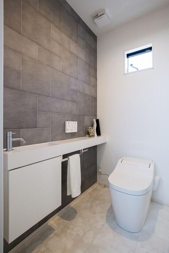 カウンターと一体の手洗器 壁の一面はエコカラットでアクセント 小さなバスルームのリフォーム トイレ おしゃれ 小さなトイレ