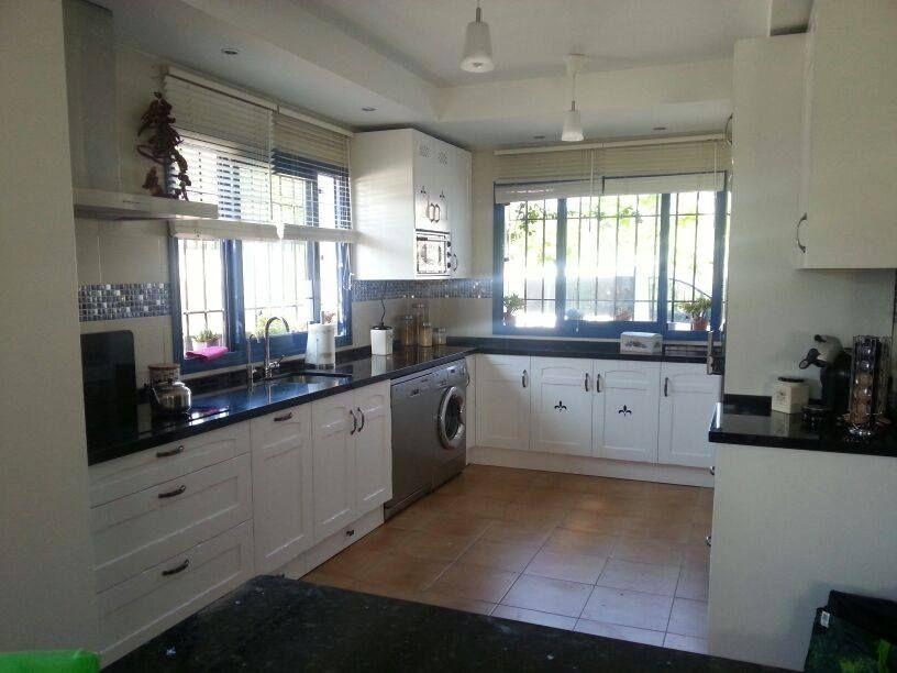 Cocina en madera de roble lacada en blanca y encimera de for Encimera de cocina lacada en blanco negro