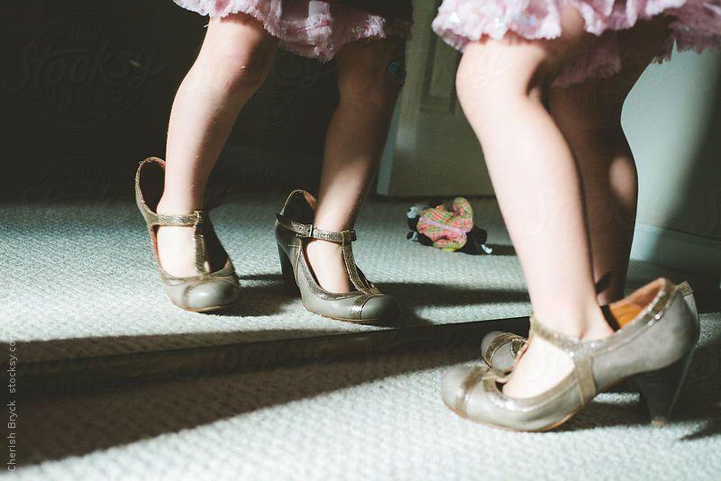 A little girl is wearing women's high heels as looks in the mirror. by Cherish Bryck