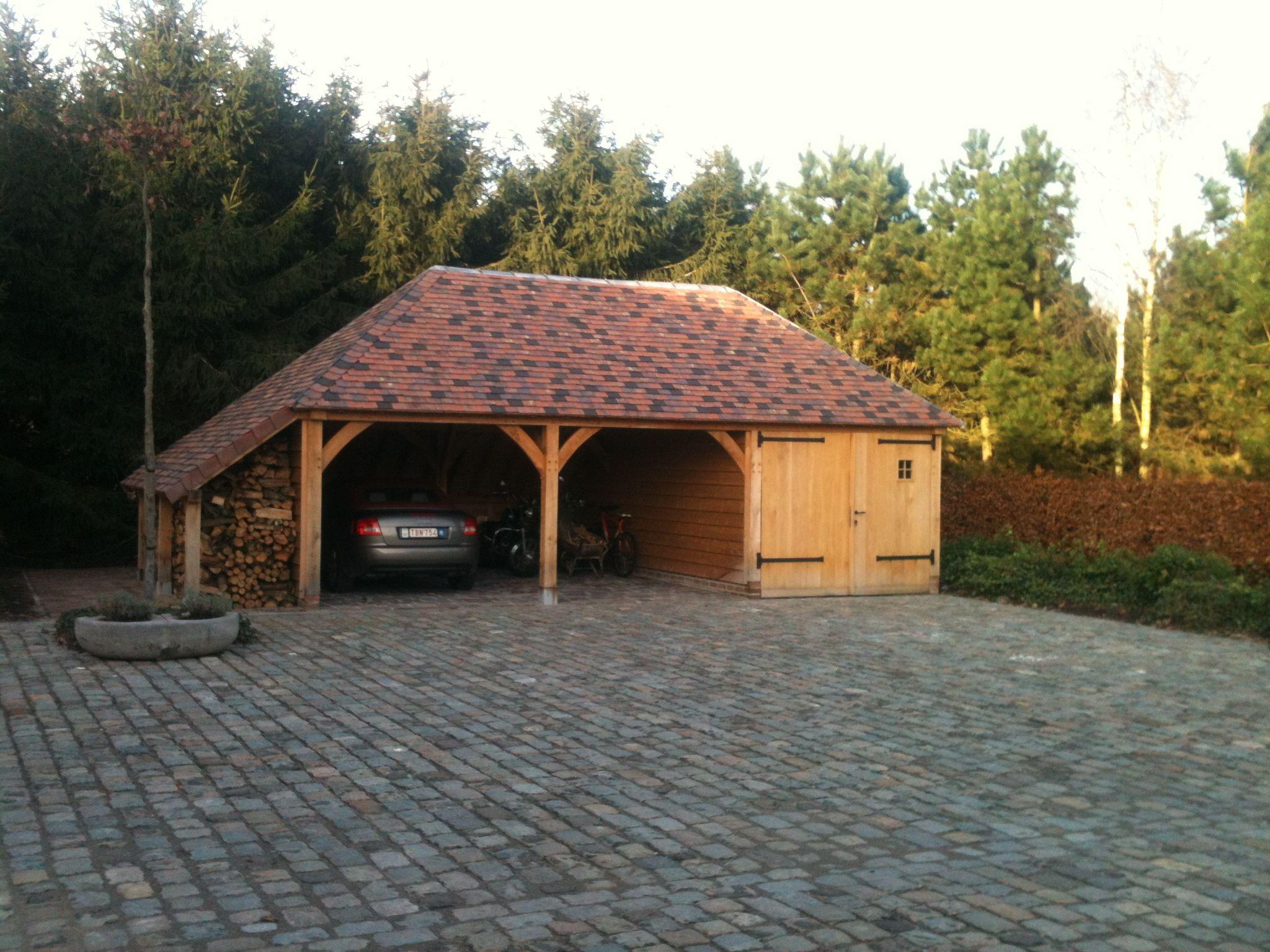 Dubbele carport met garage en houtberging. Het gebouw is afgewerkt met een schilddak waarbij is gekozen voor een nieuwe platte tegelpan met een verouderde look.