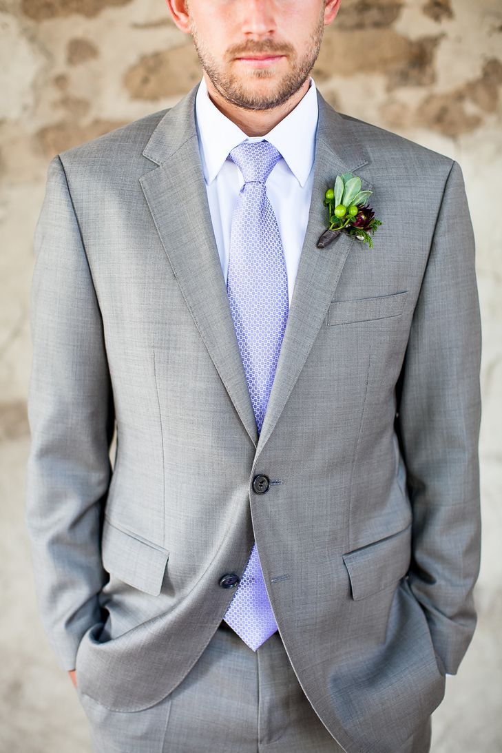 groom is dressed in a light gray suit with a light blue