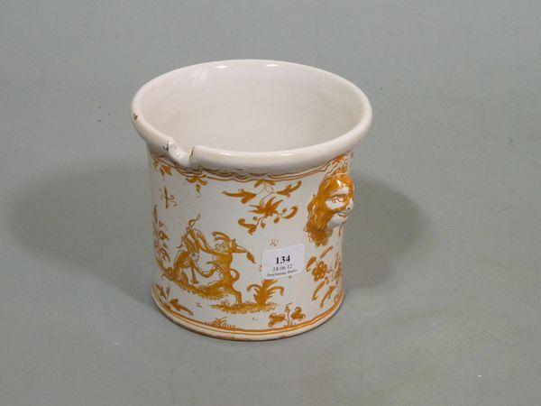 MOUSTIERS  Seau à verre cylindrique à décor en camaïeu orangé de singes grotesques et oiseau fantastique sur trois terrasses fleuries, les prises en forme de masques de satire.  XVIIIème siècle.  Hauteur : 10,5 cm.