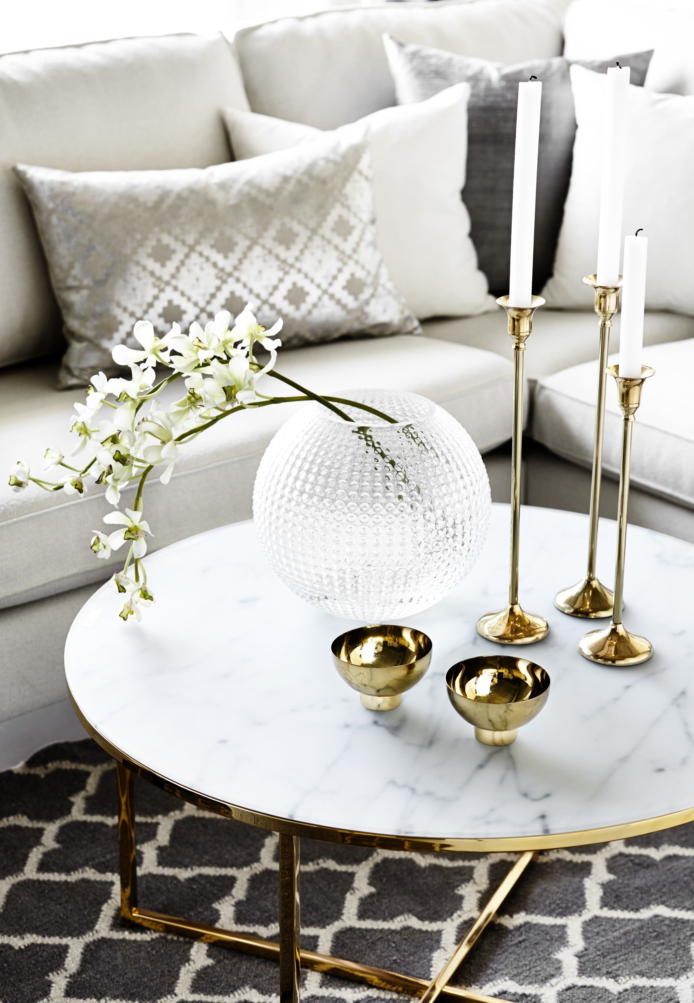 A Gold And White Living Room With A Marble Coffee Table