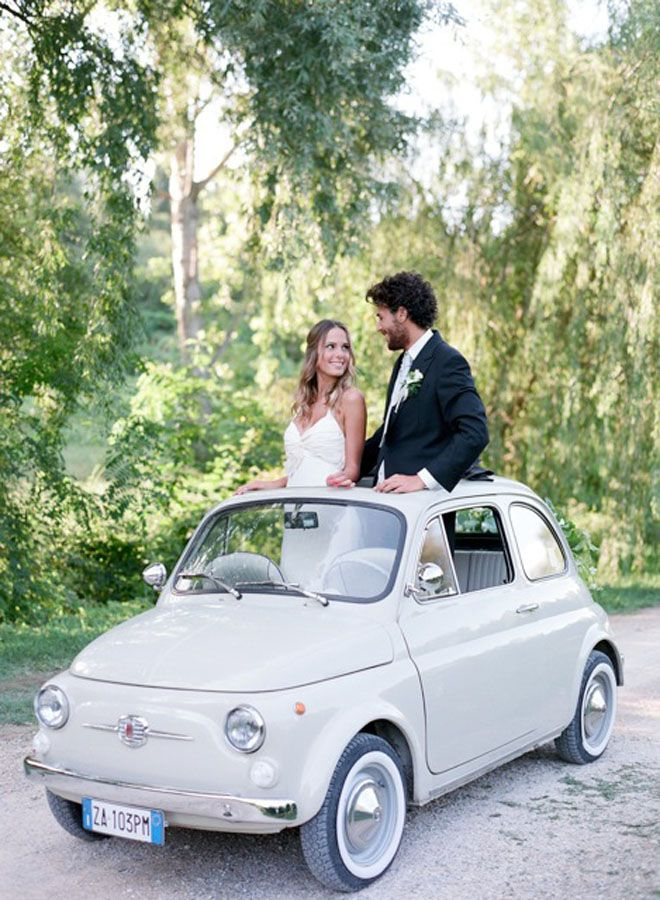 Newlywed couple in their white vintage Italian car