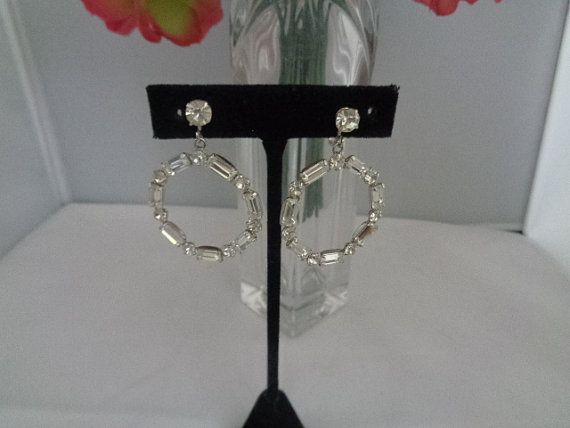Rhinestone Large Round Drop Dangle Vintage Earrings with Screw-On Backs and a Single Rhinestone on the Ear Set in Silvertone Priced at $22.00. Plus we are giving a 15% discount and free shipping to the United States only. These earrings are to die for. They are set in silvertone and are drop dangle earrings. Huge Silvertone Hoops that drop from a single rhinestone. Make it a great vintage day! Coco