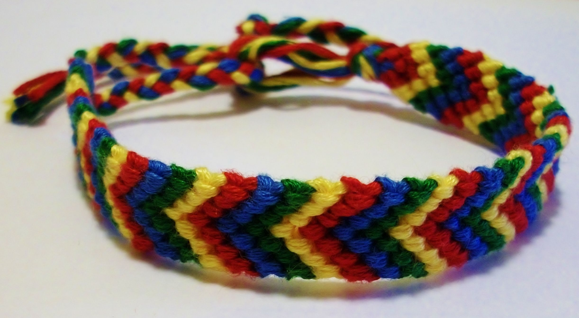 This chevron pattern friendship bracelet was made using red, yellow, green and blue embroidery floss. The length of the knotted area is 6 inches. The length of the entire bracelet is a little over 10 inches.