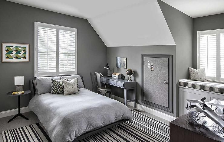 Gray kid's bedroom features walls painted charcoal gray lined with a gray  platform bed dressed in