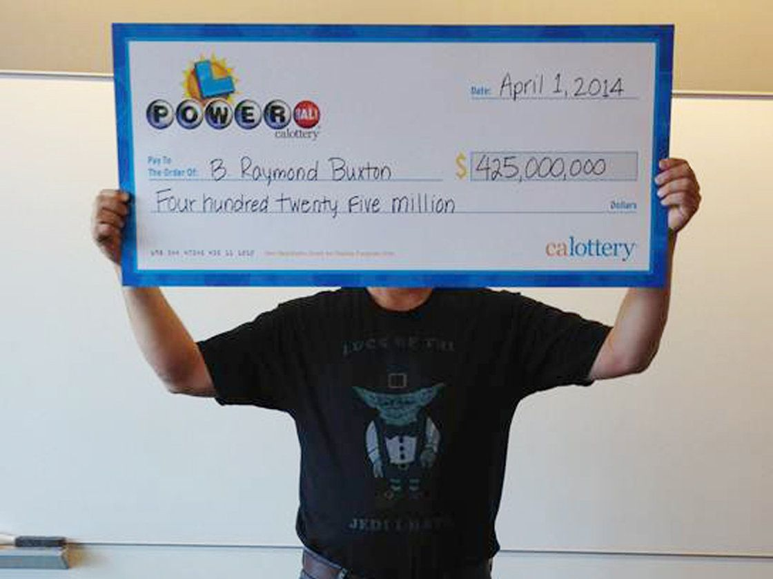 Hidden, he is: This photo provided by the California Lottery shows Powerball winner B. Raymond Buxton holding his ceremonial check.