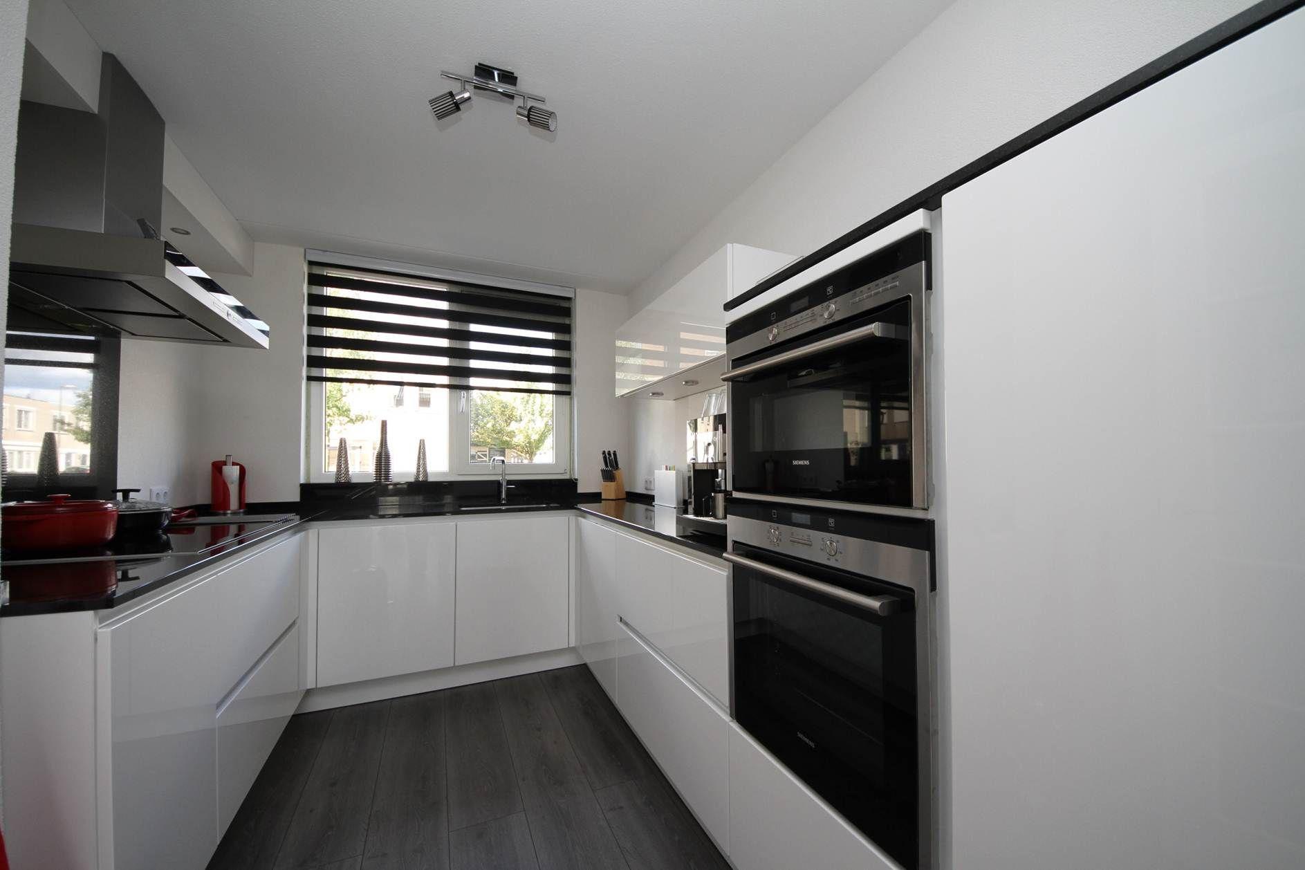 Witte hoogglans greeploze keuken met zwart gepolijst composieten