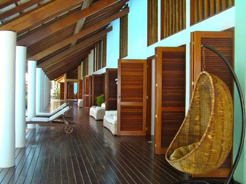 varanda com piso em madeira e telhado inclinado alto, para maior lcaridadae dentro dos cômodos