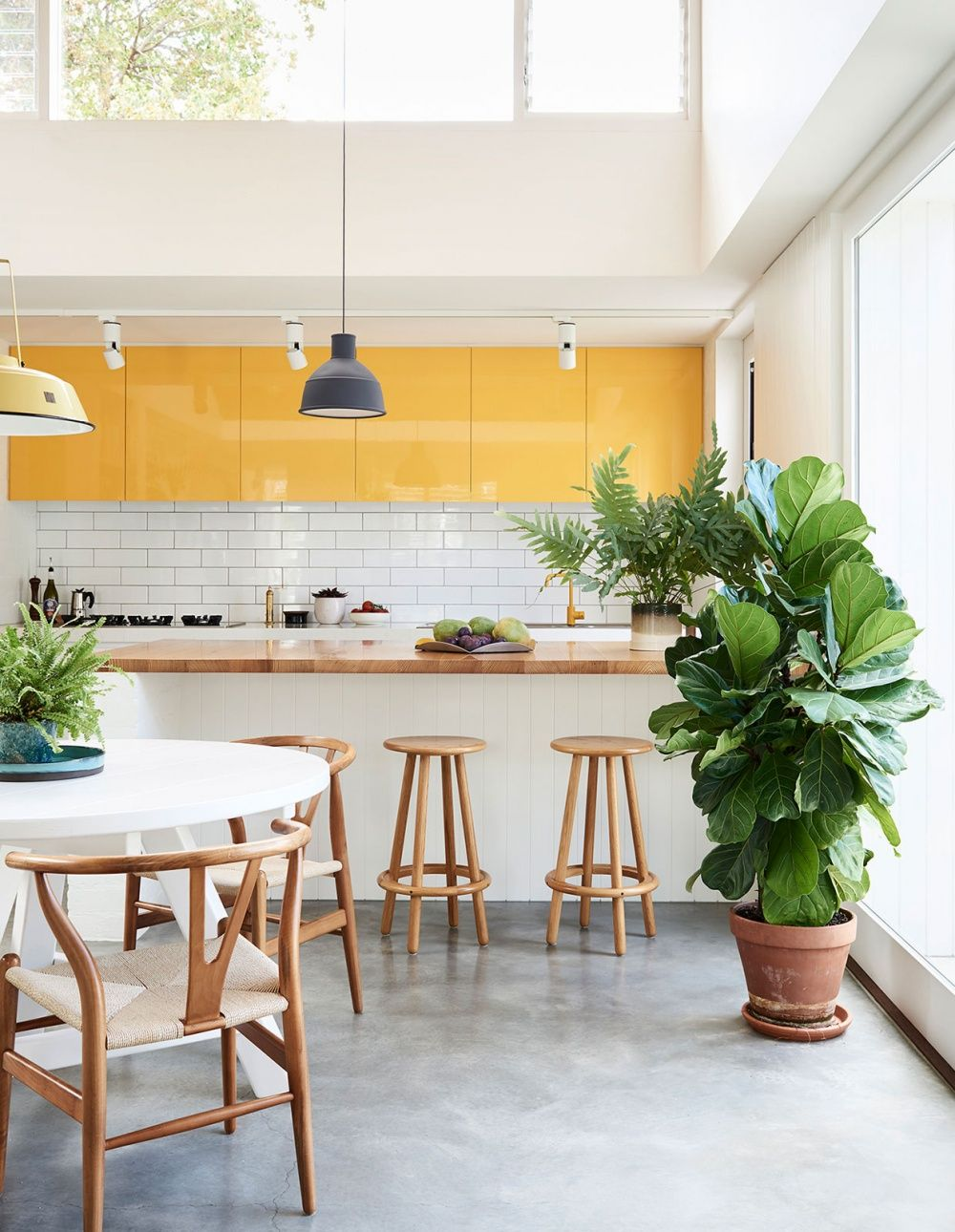sunshine bright yellow cabinets in a modern light filled kitchen with subway tile and natural wood accents mwah
