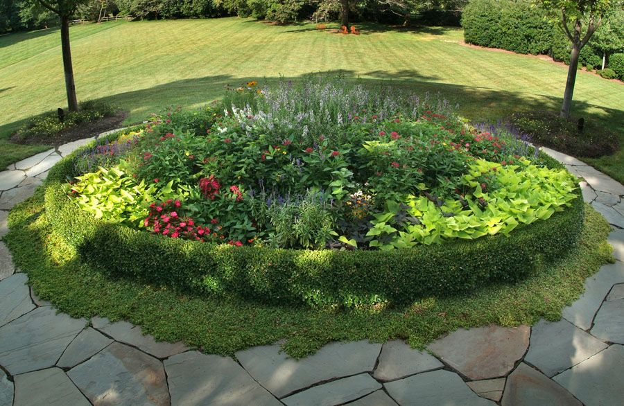 The Meticulous Planting Design In This Circular Bed Livens Up The