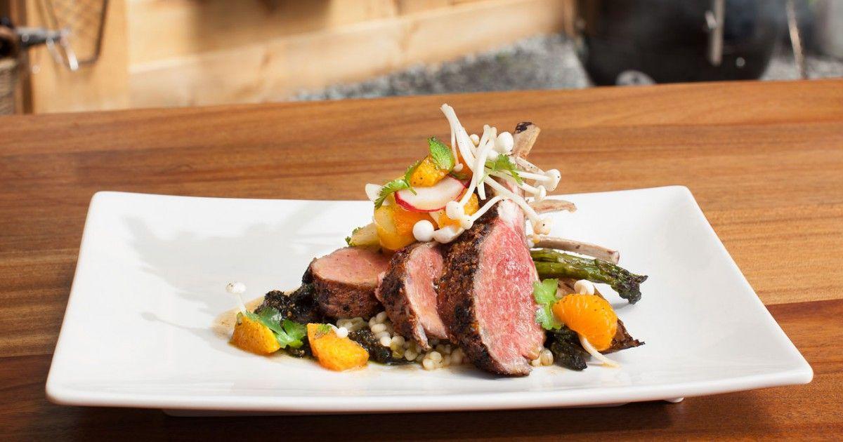 Une recette de carrés d'agneau rôtis sur planche de cèdre, salade d'agrumes et pesto de chou frisé et pistaches, présentée sur Zeste et zeste.tv