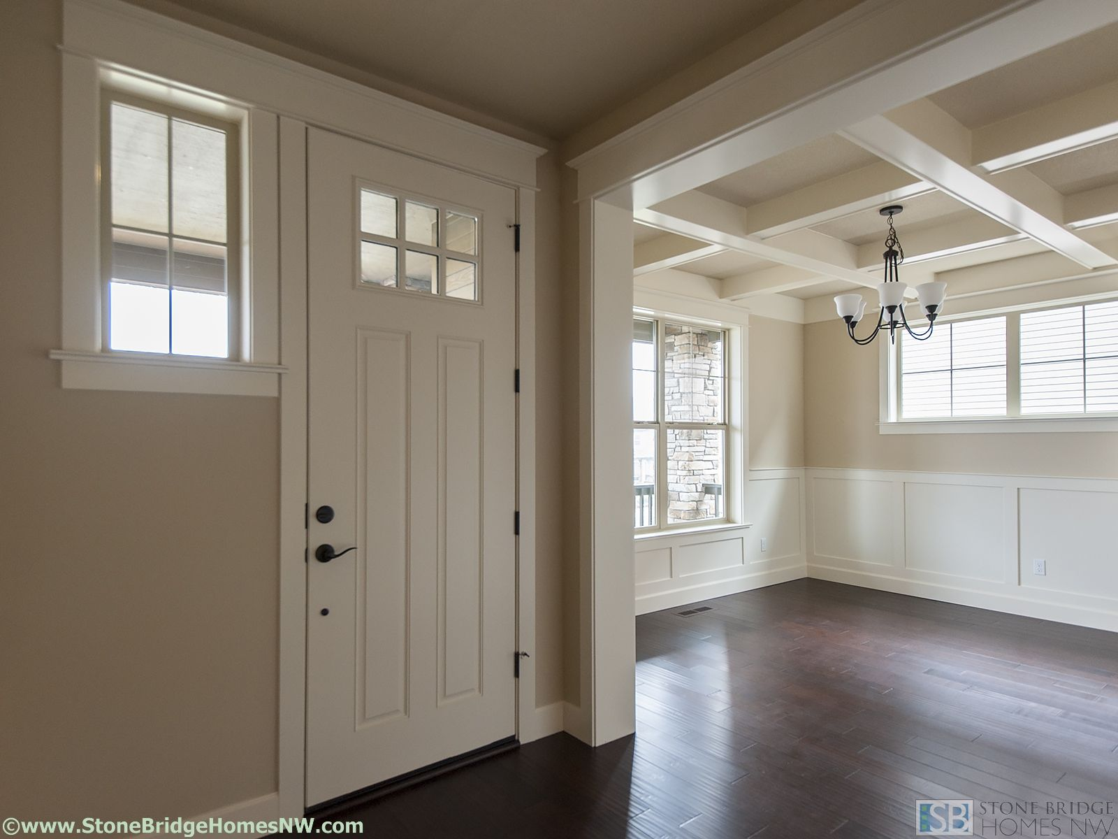 Entry into the dining room with wainscoting and coffered ceilings.