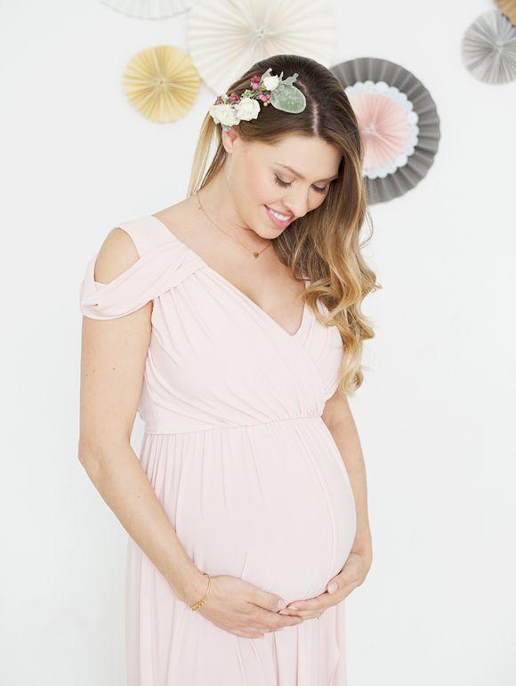 c6ef2e8c8b1 femme enceinte en robe rose qi regarde son ventre en souriant