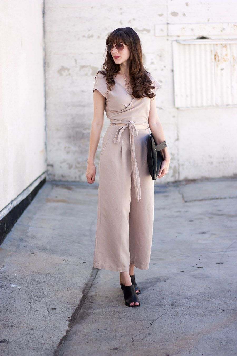 e741e96133 Minimalist summer date night outfit  Neutral linen jumpsuit with black  leather clutch and open toed mules.