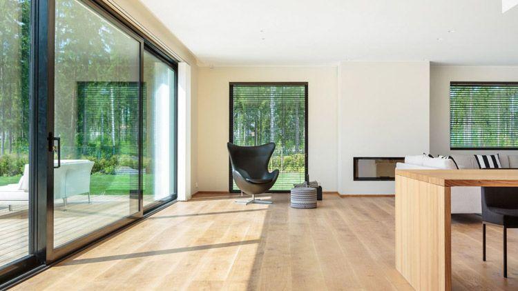Suuret ikkunat sekä liukuovi tuovat luonnon ja valon sisälle taloon.