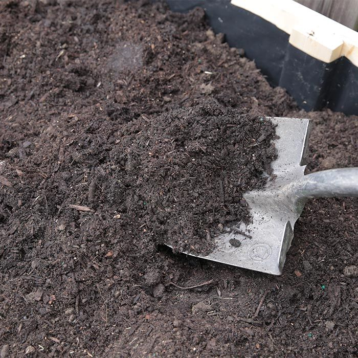 Adding Soil And Compost To The Garden Bed.